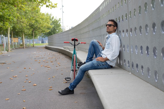 Motorista del hombre joven que se relaja en un banco mientras que escucha música Foto Premium
