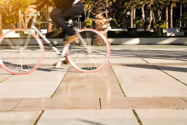 Movimiento borroso de una persona que monta la bicicleta en el parque Foto gratis