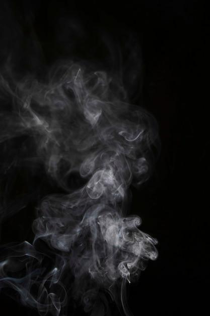 Movimiento de humo blanco transparente sobre fondo negro. Foto gratis