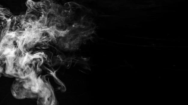 Movimiento de humo sobre fondo negro. Foto gratis
