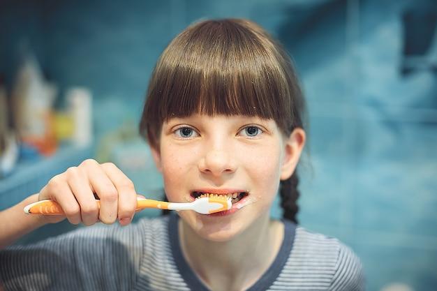 Muchacha adolescente caucásica que cepilla sus dientes en el cuarto de baño. Foto Premium