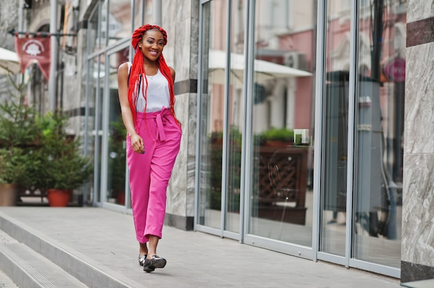 La muchacha afroamericana de moda en pantalones rosados y temores rojos plantea al aire libre. Foto Premium