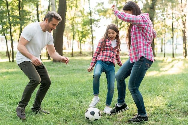 Muchacha alegre que juega el balón de fútbol con su padre en hierba en parque Foto gratis