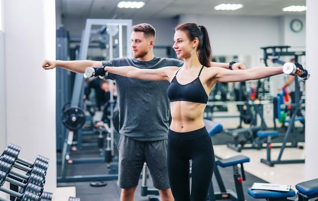 Muchacha de la aptitud que tiene entrenamiento con pesas con la ayuda del entrenador en el gimnasio. Foto Premium