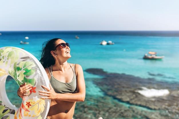 Muchacha asiática de la cacerola bastante feliz con el flotador grande y el mar azul detrás en fondo. Foto Premium