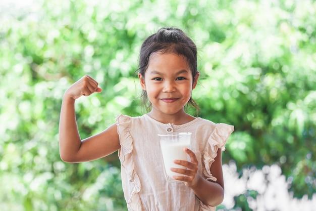 La muchacha asiática linda del niño que sostiene el vidrio de leche y hace gesto fuerte Foto Premium
