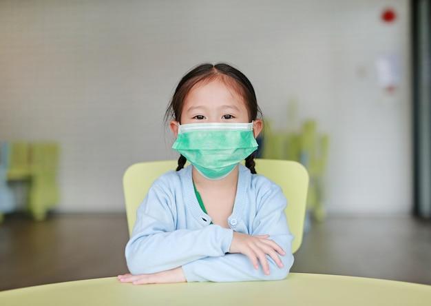 Muchacha asiática del niño que lleva una máscara protectora que se sienta en silla del niño en sitio de niños. Foto Premium