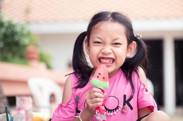 Muchacha asiática del niño que sonríe y feliz con comer el helado Foto Premium