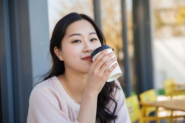 Muchacha asiática pensativa que disfruta del café para llevar en café de la calle Foto gratis