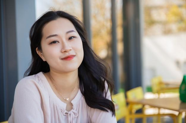 Muchacha asiática pensativa sonriente que se relaja en cafetería al aire libre Foto gratis