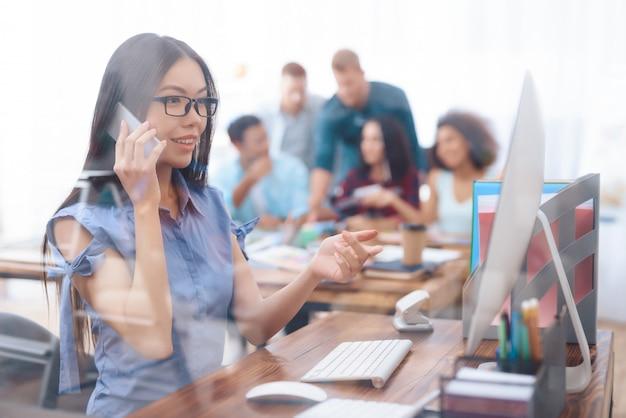 Muchacha asiática que habla en el teléfono en oficina. Foto Premium