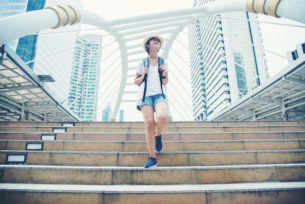 Muchacha asiática sonriente feliz del estudiante con la mochila en el fondo de la ciudad Foto gratis