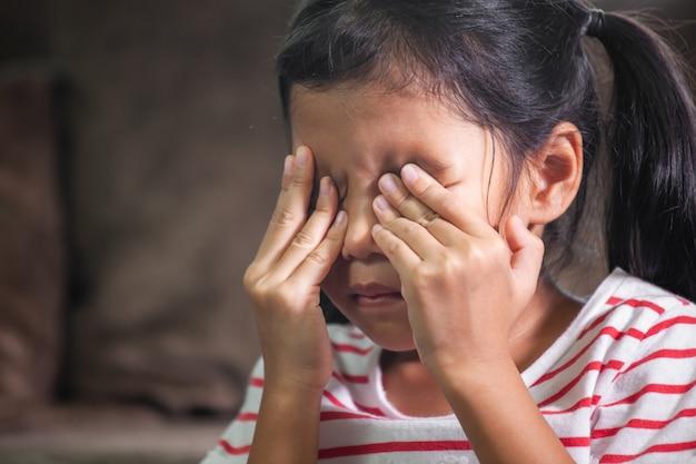 La muchacha asiática triste del niño está llorando y se está frotando los  ojos con sus manos   Foto Premium
