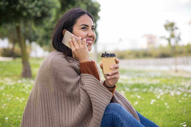 Muchacha atractiva alegre que tiene charla agradable del teléfono Foto gratis