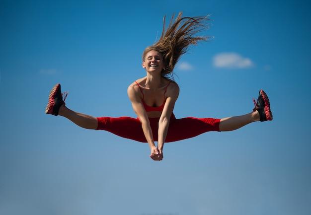 La muchacha caucásica joven realiza la guita que salta en backround del cielo. Foto Premium