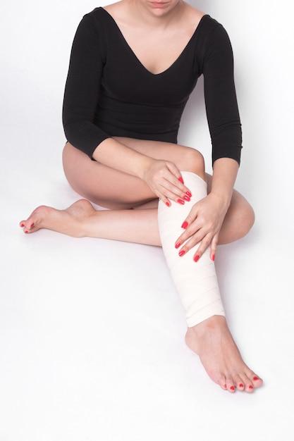 La muchacha corrige un vendaje elástico que ata Foto Premium