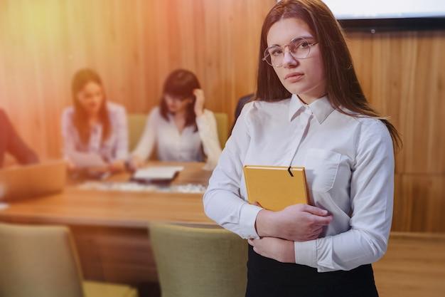 Muchacha elegante atractiva joven del oficinista en vidrios con un cuaderno en las manos en el fondo de colegas de trabajo Foto Premium