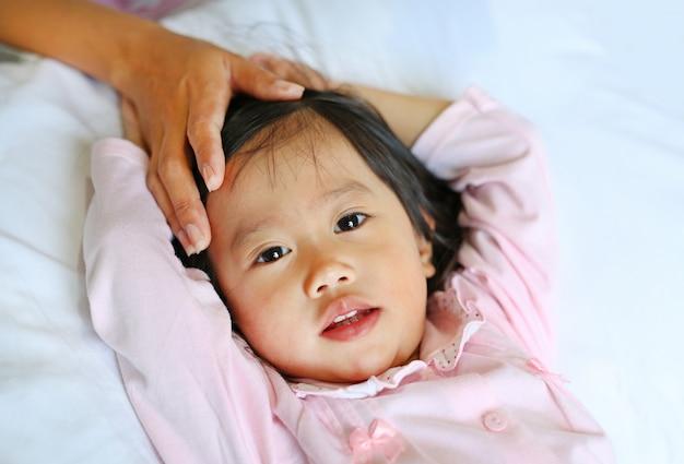 Muchacha enferma que miente en cama con la mano de la cabeza del tacto de la madre de su hija para comprobar temperatura. Foto Premium