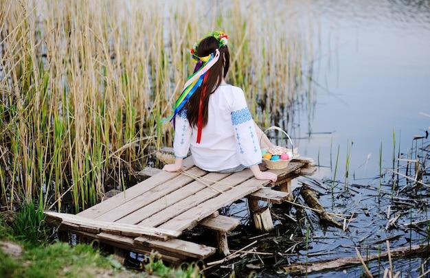 Muchacha eslava en la camisa ucraniana que se sienta en el puente con pascua Foto Premium