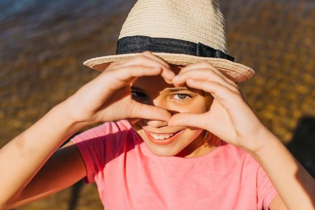 Muchacha feliz que muestra el corazón con las manos Foto gratis