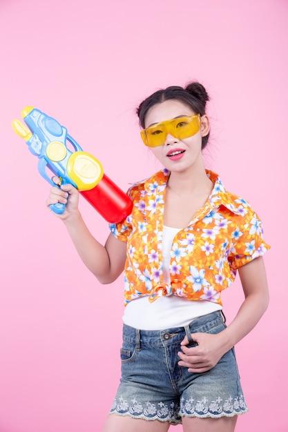 Muchacha feliz que sostiene un arma de agua rosado del fondo. Foto gratis