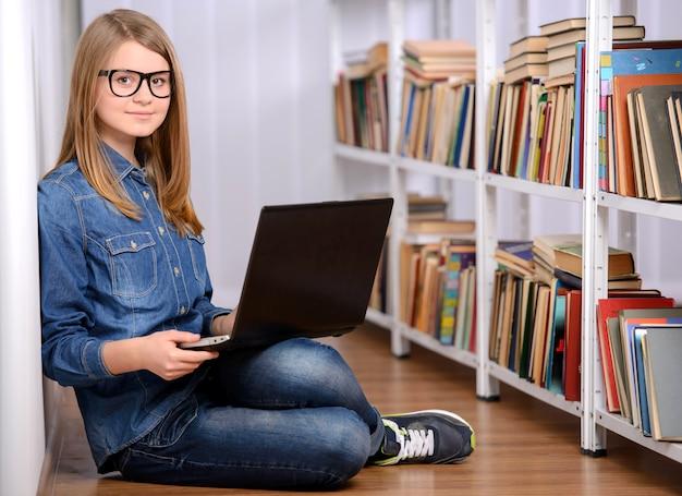 Muchacha feliz que usa una computadora portátil en la biblioteca grande. Foto Premium