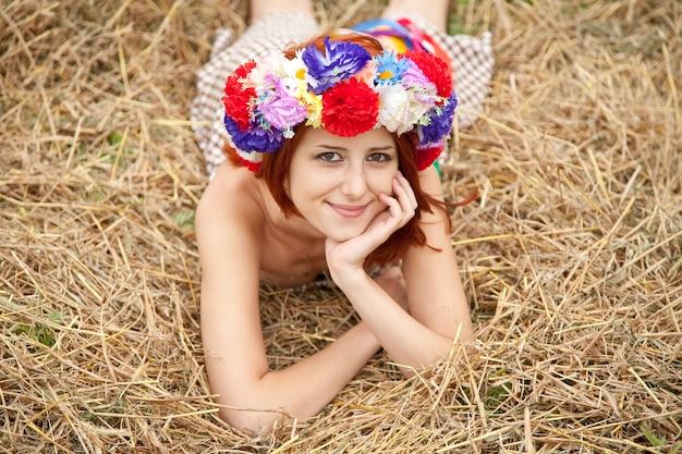Muchacha en la guirnalda nacional eslava que miente en el campo. Foto Premium