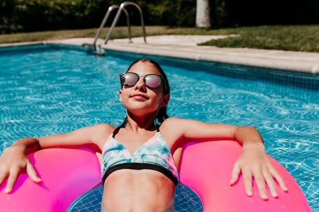 Muchacha hermosa del adolescente que flota en los anillos de espuma rosados en una piscina. con gafas de sol y sonriendo. diversión y estilo de vida veraniego Foto Premium