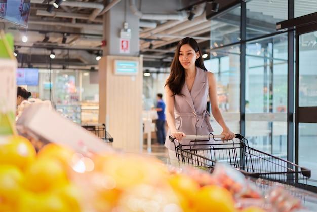 La muchacha hermosa asiática joven está eligiendo las frutas en supermercado. Foto Premium