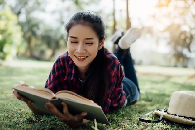 Muchacha hermosa en el bosque del otoño que lee un libro Foto gratis