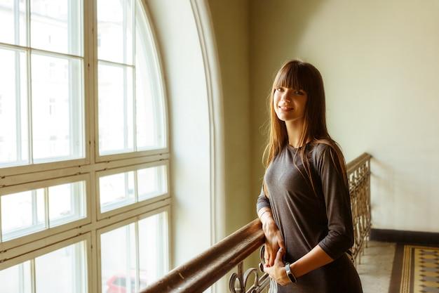 Muchacha hermosa joven que se coloca cerca de la sonrisa de la ventana. Foto Premium