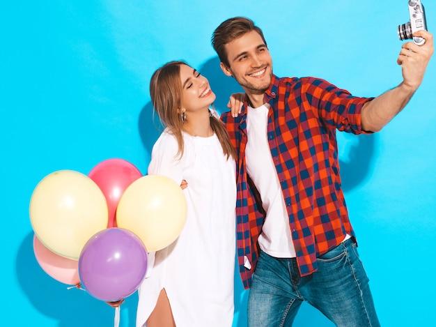 Muchacha hermosa sonriente y su novio hermoso que sostiene el manojo de globos coloridos. feliz pareja tomando foto selfie de sí mismos en la cámara retro. feliz cumpleaños Foto gratis