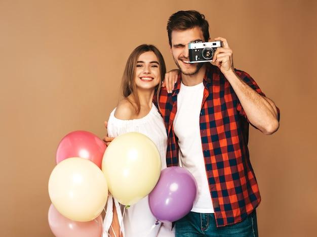 Muchacha hermosa sonriente y su novio hermoso que sostiene el manojo de globos coloridos. feliz pareja tomando fotos de sí mismos en la cámara retro. feliz cumpleaños Foto gratis