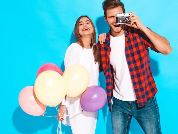 Muchacha hermosa sonriente y su novio hermoso que sostiene el manojo de globos coloridos. feliz pareja tomando fotos de sí mismos. feliz cumpleaños Foto gratis