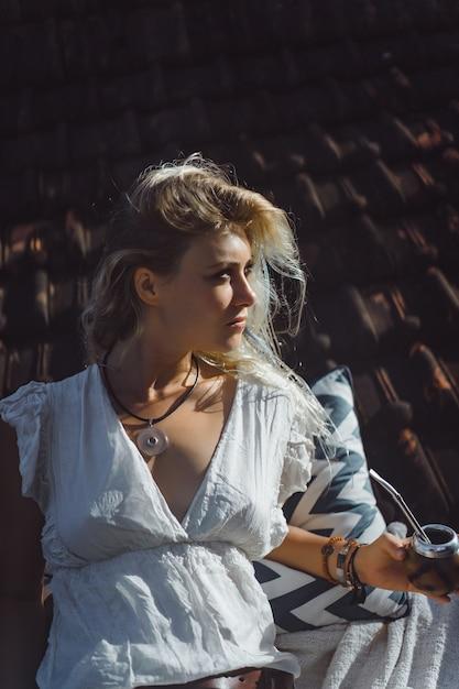 Muchacha india hermosa del hippie con el pelo rubio largo en el té de consumición del compañero del tejado. Foto gratis