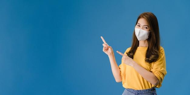 La muchacha joven de asia usa una mascarilla médica que muestra algo en el espacio en blanco con vestida con un paño informal y mira a la cámara. distanciamiento social, cuarentena por coronavirus. bandera panorámica de fondo azul. Foto gratis