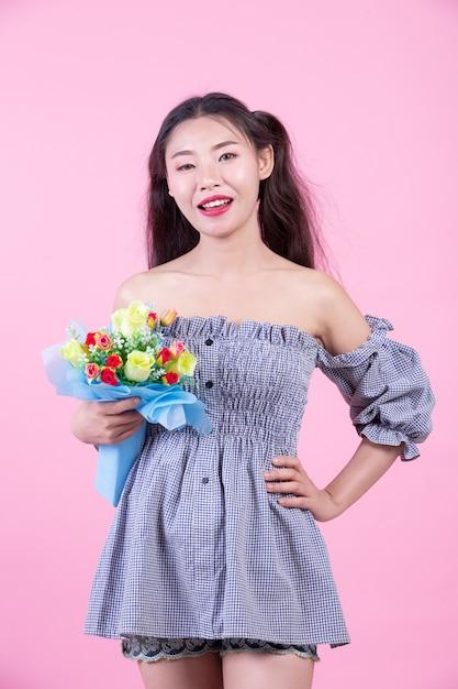 La muchacha de la moda se viste para arriba con gestos de mano en un fondo rosado. Foto gratis