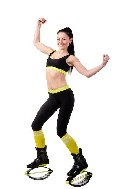 La muchacha morena sonriente en kangoo salta los zapatos que muestran músculos en sus manos. Foto Premium
