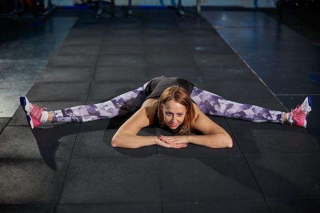 Muchacha muscular hermosa en las polainas grises que hacen estirar. pabellón deportivo en estilo industrial. Foto Premium