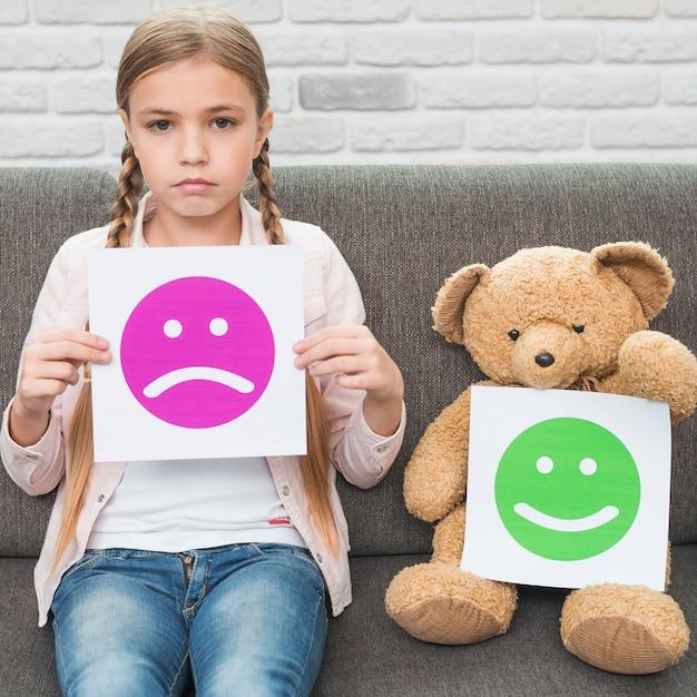 Muchacha y oso de peluche que sostienen el papel triste y feliz de los emoticons de la cara que se sienta en el sofá Foto Premium