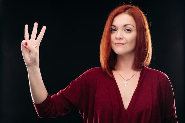 Muchacha pelirroja atractiva que lleva a cabo la mano con tres dedos para arriba. Foto Premium