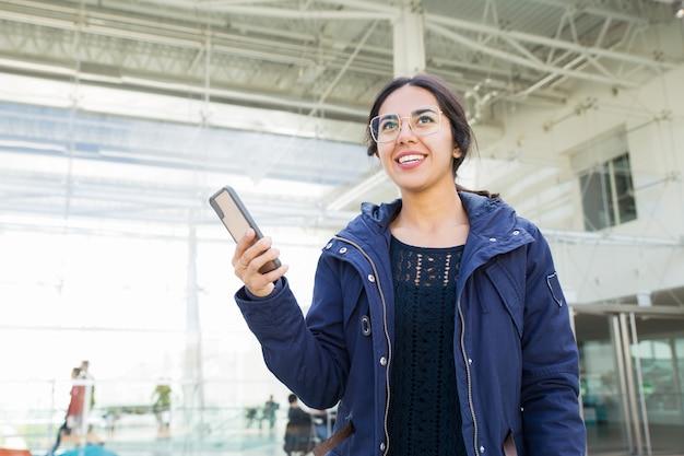 Muchacha positiva sonriente que usa el teléfono al aire libre Foto gratis