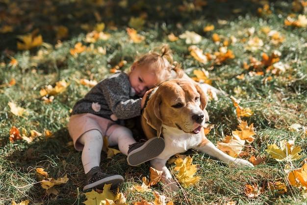 Muchacha que miente en su perro del beagle en el parque Foto gratis