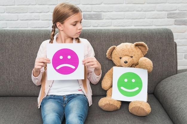 Muchacha que sostiene el papel triste de los smiley que mira el oso de peluche con smiley felices Foto Premium