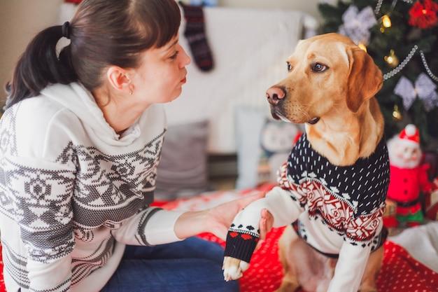 Muchacha que sostiene una pata de perro puntero en ropa de navidad con un árbol de navidad y decoraciones. concepto de mascotas de navidad. Foto Premium