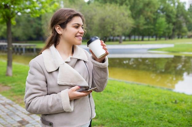 Muchacha relajada sonriente con el teléfono que bebe el café sabroso Foto gratis