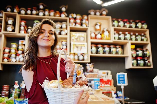 Muchacha en rojo que sostiene diversos productos en cesta en tienda de la tienda de delicatessen. Foto Premium