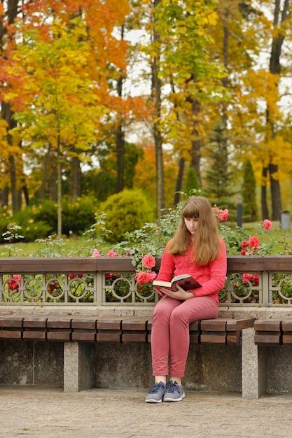 La muchacha está sentada en el banco y leyendo el libro, otoño. Foto Premium