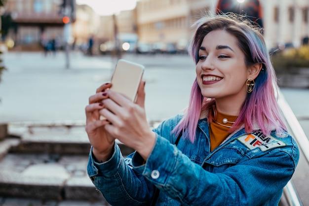 Muchacha sonriente del inconformista que toma el selfie en la calle de la ciudad. Foto Premium
