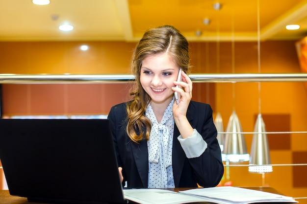 Muchacha sonriente joven que se sienta en un café con un ordenador portátil y que habla en el teléfono celular Foto Premium